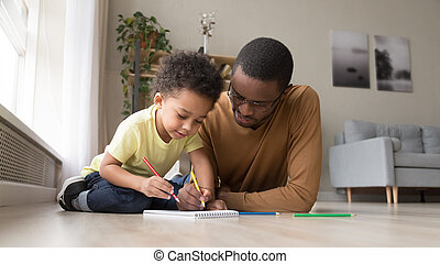 Black dad and little son drawing in album together