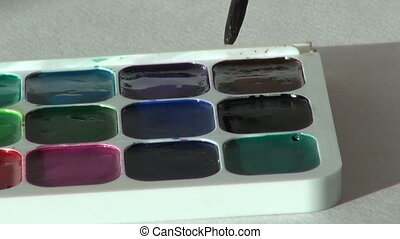 black dark color. close up. Artist works with brush and...