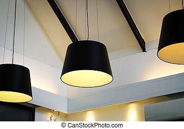 Black decorative lamp hanging from the ceiling, modern lamp on white background