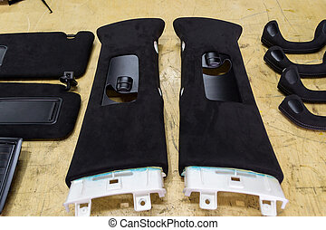 Black drains and ceiling handles with audio speakers removed from the car for tuning and bracing with black soft material on a table in the workshop for working with the interior of vehicles