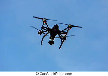 Black drone quadcopter with camera flying over blue sky. Angle view