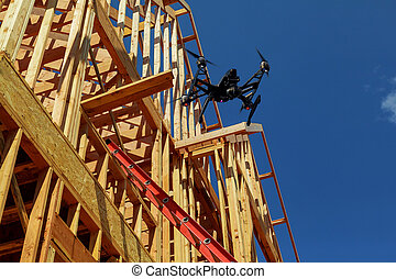 Black drone quadcopter with camera flying over New Houses Being Built In North America