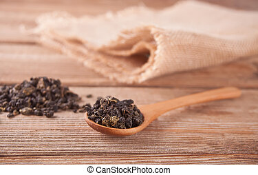 Black dry tea leaves with wooden spoon on the wooden table