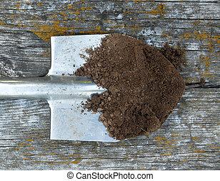 Black earth on the metal spade