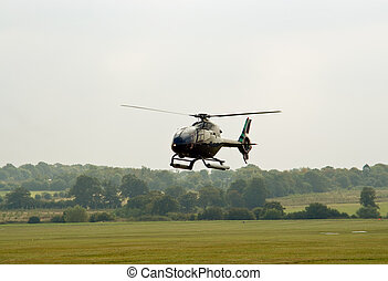 Black EC-120 hovering before landing on the airfield