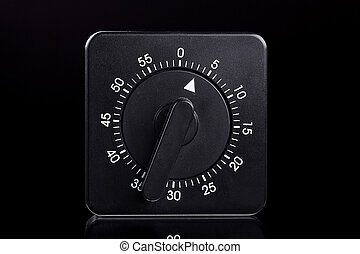 black egg timer with a reflection on grey background