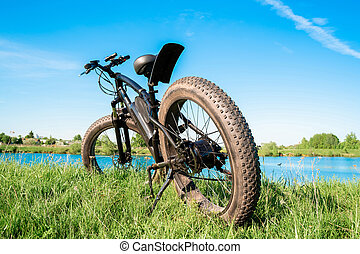 Black electric bike with thick wheels on the grass near the lake. Fatbike