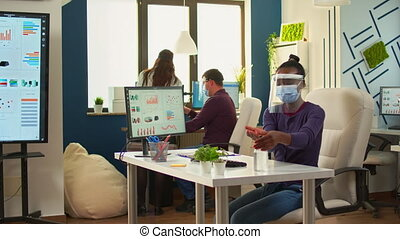 Black employee with protection mask and visor cleaning hands with sanitizer gel before writing at computer. Businesswoman in new normal workplace disinfecting while colleagues working in background