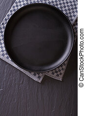 black empty plate on the table. top view vertical