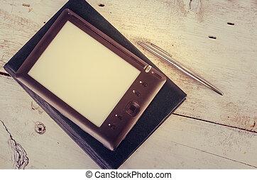 Black ereader with notebook and ink pen