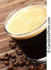 black espresso coffee in a short glass with coffee beans on wooden background