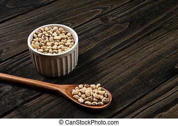 black-eyed beans in pot. Wooden black background