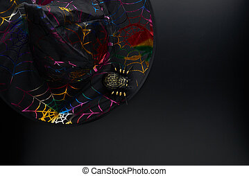 Black fabric pointed cone shaped witch or wizard hat and spider on dark background. Halloween holiday concept. Flat lay, top view, copy space..
