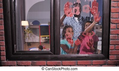 African american dad with mixed race girls making red handprints on window glass with BLM inscription on it. Family of activists supporting Black Lives Matter movement against racism, for human rights