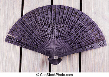 Black fan over wooden table