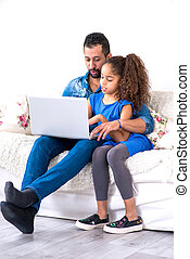 Black father and his daughter siting on a couch with a laptop