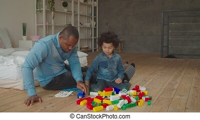 Black father and son plaiyng with building blocks