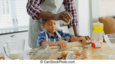 Black father and son rolling dough with rolling pin at home ...