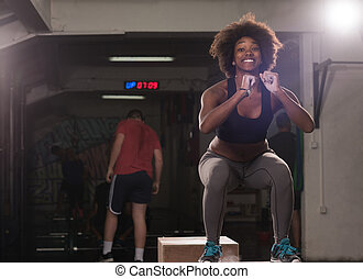 black female athlete is performing box jumps at gym