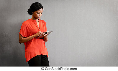 Black female entrepreneur busy using a tablet against textured wall