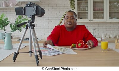 Black female food blogger recording vlog in kitchen - ...