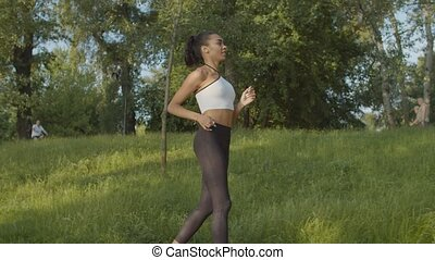 Black female jogger running in public park at dawn