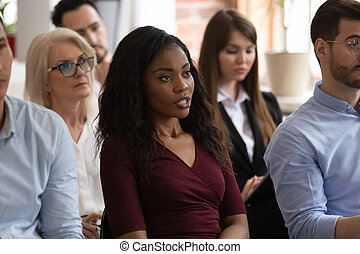 Black female professional ask question at group seminar lecture event