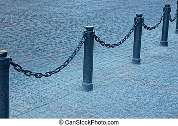 black fence with iron chains and pillars on the sidewalk on the city street