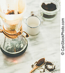 Black filtered coffee in Chemex on grey marble table...