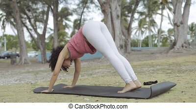 Black fit girl on mat - Side view of concentrated young...