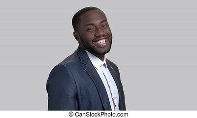 Black flirtatious businessman on grey background. Portrait of joyful dark-skinned macho-man. Invitation for a date gesture.