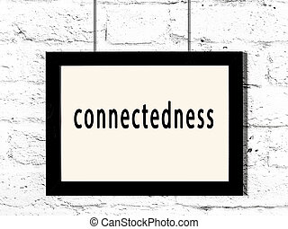 Black frame hanging on white brick wall with inscription connectedness