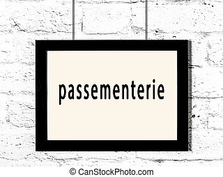 Black frame hanging on white brick wall with inscription passementerie