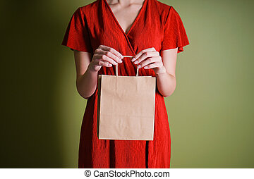 Black friday concept. Sale. Paper bag in female hands, on a green background. Copy space.