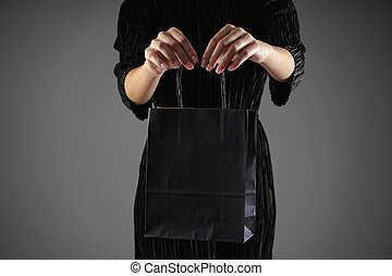 Black friday concept. Sale. Paper blue package in female hands, on a gray background. Copy space.