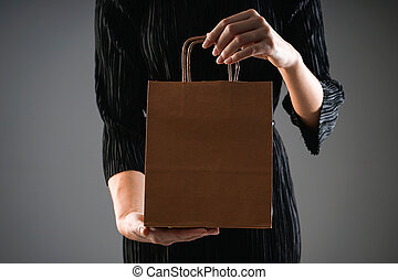 Black friday concept. Sale. Paper package in female hands, on a gray background. Copy space.