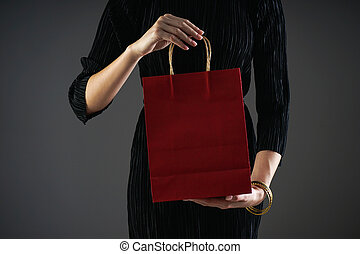 Black friday concept. Sale. Paper red package in female hands, on a gray background. Copy space.