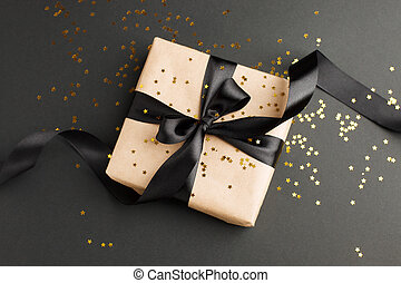 Black Friday sale flat lay with stylish gift box present and ribbon with gold star glitter on black background, flat lay, top view, copy space, xmas and holidays concept