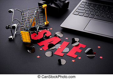 Black friday sale in red letters. Yellow candy cart and gift, laptop on black background