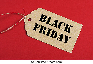 Black Friday Sale message sign on brown paper sale tag on red background.