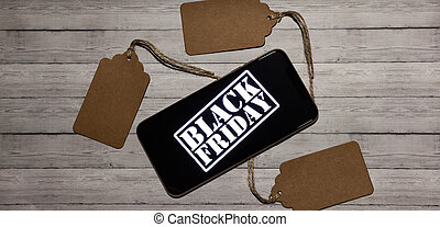 Black friday sale shopping concept with phone on wooden background