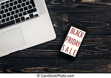 black friday sale. special offer discount text on mobile phone screen message on seasonal rustic background