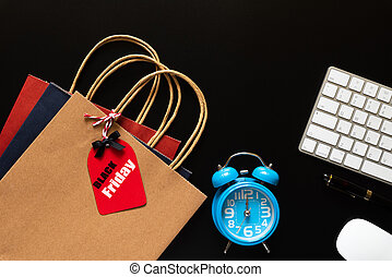 Black Friday Sale text on a red tag with keyboard computer, mouse and Alarm Clocks on black background. Shopping concept.