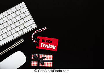 Black Friday Sale text on a red tag with keyboard computer, mouse and gift box on black background. Shopping concept.