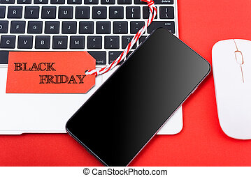 Black Friday Sale text on red tag have mobile smart phone over laptop computer