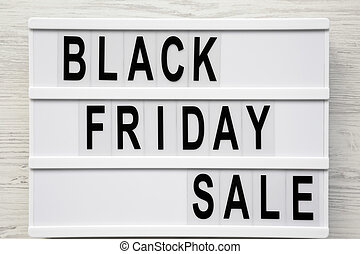 'Black friday sale' word on lightbox over white wooden surface, top view. From above, overhead.