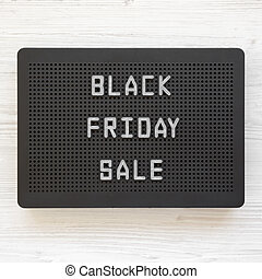 'Black Friday Sale' words on a black lightbox on a white wooden background, top view. From above, overhead, flat lay.