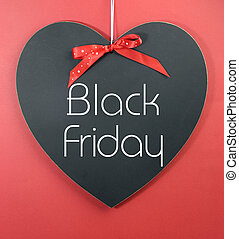 Black Friday shopping sale concept with message on a heart shape blackboard against a red background.
