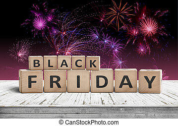 Black friday sign on a wooden table with fireworks