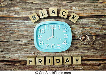 Black Friday with Clock on wooden background